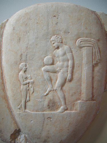 ancient Greek carving man with ball