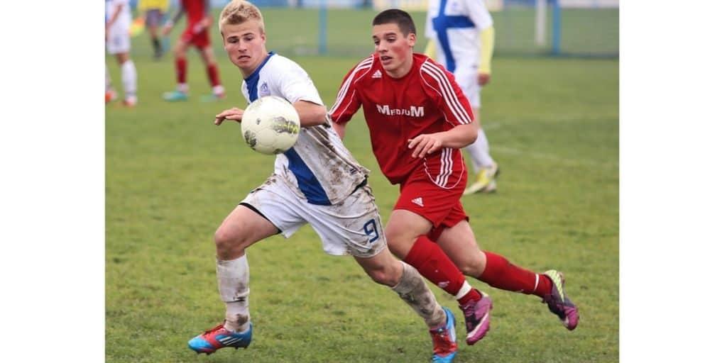 midfielder battling for ball