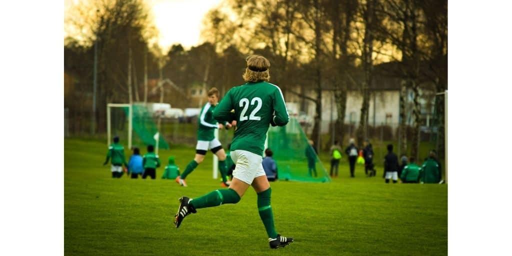 Midfielder in green jersey running on soccer field