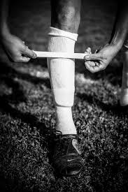 black and white photo of player wrapping tape around socks