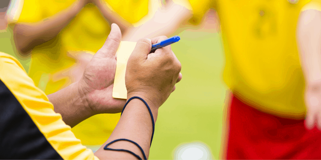 Soccer referee writing on yellow card